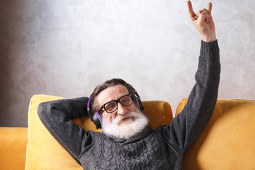 Senior handsome bearded man in glasses wearing grey pullover sitting in headphones on a yellow sofa in his light living room, relaxing and listening his favorite rock music song, modern technology
