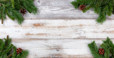 Christmas Evergreen branch decorations in all corners on white vintage wooden boards