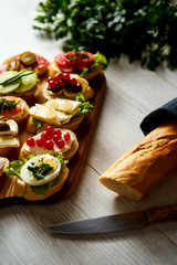 wooden board with colorful mini sandwiches or tapas along with a knife baguette and parsley on a light table