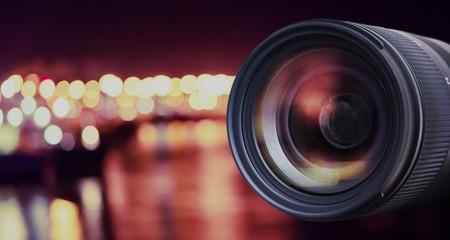 Lens of digital dslr camera and blured defocused lights in background.