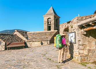 Pilgrim hiker woman with backpack in small town Fotomurales