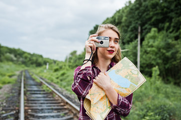 Portrait of a gorgeous young girl in tartan shirt taking pictures with camera on the railway.