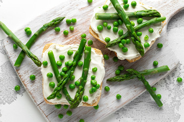 Appetizer bruschetta, toast with Asparagus, Peas and creamy soft cheese. on white board.