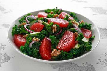 Healthy vegan, vegetarian Grapefruit kale salad with walnuts, red onion and cucumber on white background