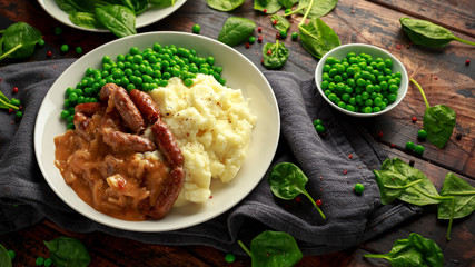 Mashed potatoes and sausages, bangers with onions gravy, green peas