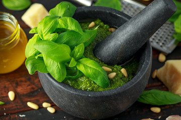 Green Basil Pesto in marble mortar with parmesan cheese, pine nuts, garlic and lemon.