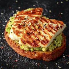 Avocado and grilled haloumi cheese toast with nigella and sesame seeds. healthy breakfast