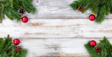 Christmas Evergreen branches and red ball decorations in all corners on white vintage wooden boards