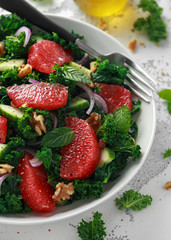 Healthy vegan, vegetarian Grapefruit kale salad with walnuts, red onion and cucumber