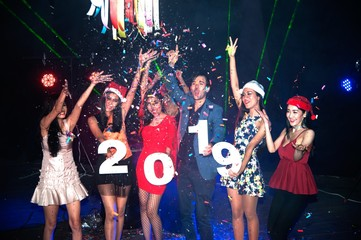 Group of people dancing at night club with Santa hat Christmas holidays party friendship relaxing celebrating new year 2019.