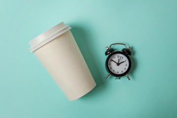Simply flat lay design paper coffee cup and alarm clock on blue pastel colorful trendy background. Takeaway drink and breakfast beverage. Good morning wake up awake concept. Top view copy space