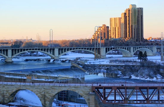 Urban city architecture background. Beautiful winter morning in Minneapolis. Cityscape with bridges over Mississippi river and Saint Anthony Falls. Minnesota, Midwest USA.