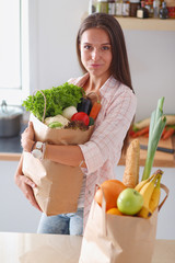 Young woman holding grocery shopping bag with vegetables. Young woman