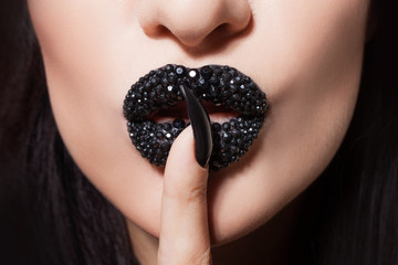 Women's lips with black lipstick and rhinestones make tin Shhh. Black lipstick and black and white manicure