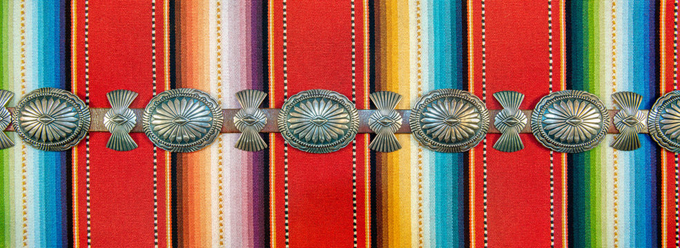 Sterling Silver Native American Concho Belt on Brightly Colored Southwestern Pattern Fabric.
