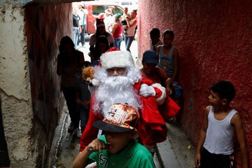 """Richard Gamboa, dressed up as Santa Claus, walks in an alley at the slum Cota 905 during the event """"Santa en las calles"""" (Santa in the streets) in Caracas"""