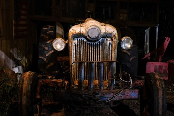 An operational antique or vintage tractor in an old dimly lit barn. Angle gives the tractor an evil or mean appearance.