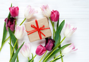 colorful beautiful tulips and gift box on the white wooden table. Valentines, spring background. floral mock up with copyspace. happy mothers day, romantic still life, fresh flowers