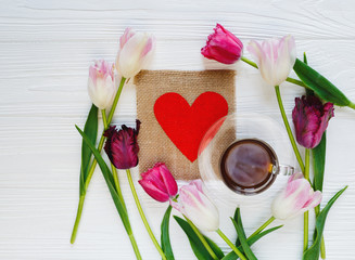 colorful beautiful tulips coffee cup wooden heart on the white wooden table. Valentines, spring background. floral mock up with copyspace. happy mothers day, romantic still life, fresh flowers