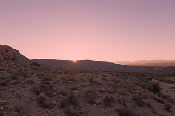 Stunning panorama of Mojave Desert at sunset. Rocky terrain with sparse vegetation and mountains chain on horizon.