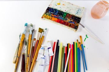 work space on a table with pencils and paintbrushes