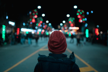 boy in wool hat looking down a street decorated with christmas lights Fotomurales