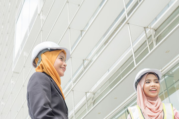 Professional woman engineers are discussing on construction at outdoor.