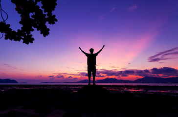 Alone man standing holding his hand up and see landscape scenery view in sunset time