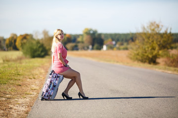 young woman hitch-hiking on a road with luggage bag at the fields. girl is sitting on baggage and waiting for the car to leave the village