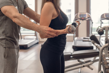 Fitness instructor helping sporty woman with lifting dumbbells
