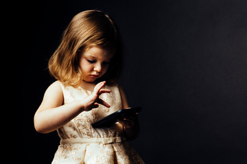 Portrait of a small toddler girl using a  smartphone, isolated on black studio background