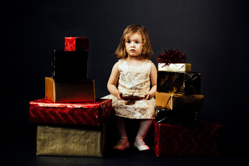 Portrait of a small toddler girl surrounded with gifts, isolated on black studio background