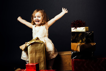 Portrait of a very happy toddler girl with both arms up and surrounded with gifts, isolated on black studio background