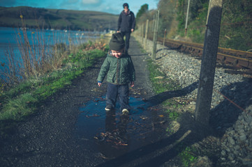 Toddler and grandfather walking by railway tracks
