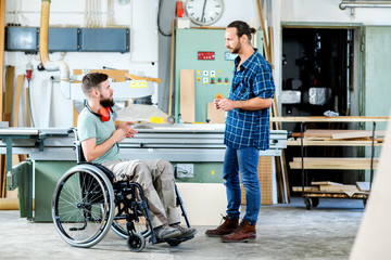 worker in wheelchair in a carpenter's workshop with his colleague in conversation