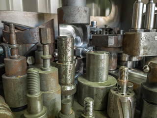 A lot of old rusted machining stock holders dark industrial back