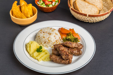 Turkish Kofte on a plate with rice, potatoes and vegetables, accompanied by bread, French fries and salad, on a black background
