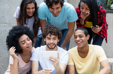 Group of international young adults gaming with phone