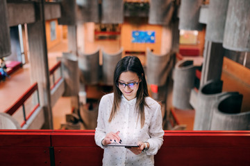 Beautiful smiling female college teacher with eyeglasses and brown hair standing in the college building and using tablet.