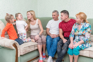 Grandparents, children and granddaughters play on couch