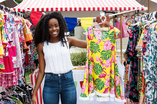 Beautiful african american woman selling clothes at market