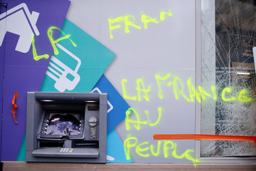 """A message, """"France to the People"""" is seen on a vandalized bank the morning after clashes with protesters wearing yellow vests, a symbol of a French drivers' protest against higher diesel taxes, in Paris"""