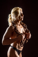 Athletic woman with rusty chain. Attractive fitness lady with long blond hair showing her muscles