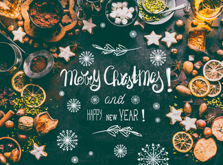 Merry Christmas greeting card with text lettering , spices, chocolate and cookies on dark background with sweet food ingredients: nuts, dried fruits, broken chocolate, cookies and winter spices