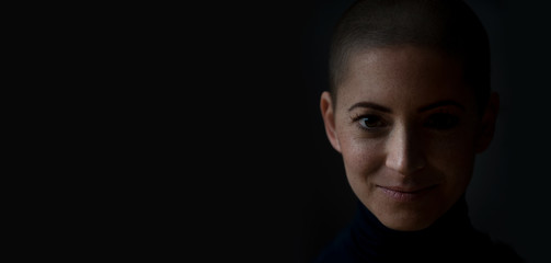 Portrait of a beautiful young courageous smiling female cancer patient, with shaved head. Gorgeous woman, a cancer patient, portrait on dark background with copy space.