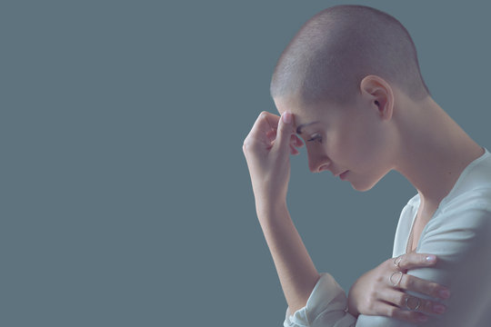 Sad, frightened and depressed female cancer patient portrait with copy space. Breast cancer patient, head in hands, portrait.