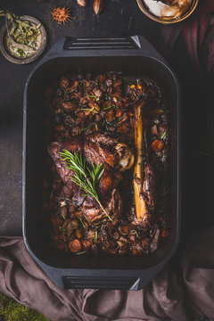 Slow cooked venison roast in black cast iron pan, top view. Braised leg of deer with bone and roasted vegetables in pot on dark rustic kitchen table background, top view