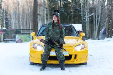 Cool sexy red hair girl in camouflage with paintball gun sitting on sport car bonnet
