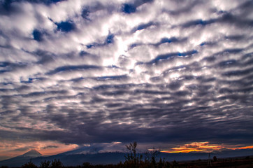 Accumulation layered-cumulus heavy clouds on the darkening autumn sky in the valley of mount Ararat