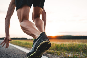 Close up view on strong and muscular athlete runner feet in start pose on asphalt road outdoor. Blurred background
